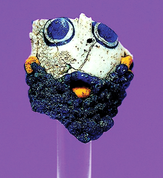 Uno degli elementi di collana in pasta vitrea raffigurante un volto umano barbato (fine VI - V sec. a.C.).